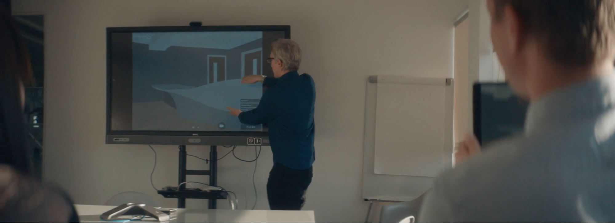 Person presenting with a big screen, the screen has images of the inside of a building, is in the background of the image and in the foreground are the shoulders of two people sitting next to each other watching the presentation.