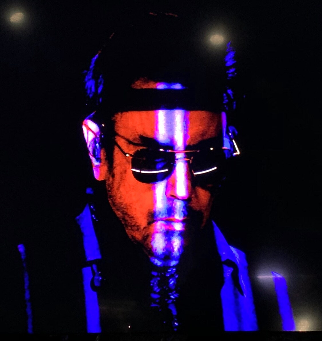 Portrait of the musician Jean Michel Jarre wearing sunglasses and a black headband with blue and red light streaking on his face and dark backlighting