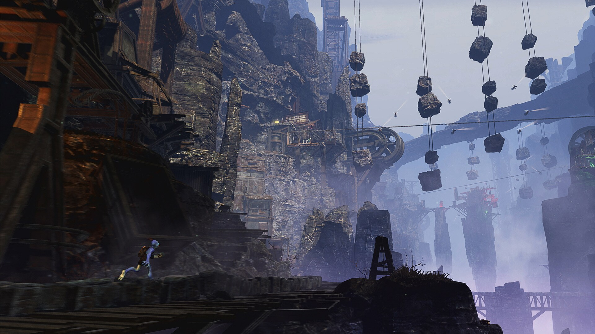 Taken from Oddworld Soulstrom game - Person running along a rocky mountainous type area. ahead of them are large stone bridges and large boxes hanging from wires