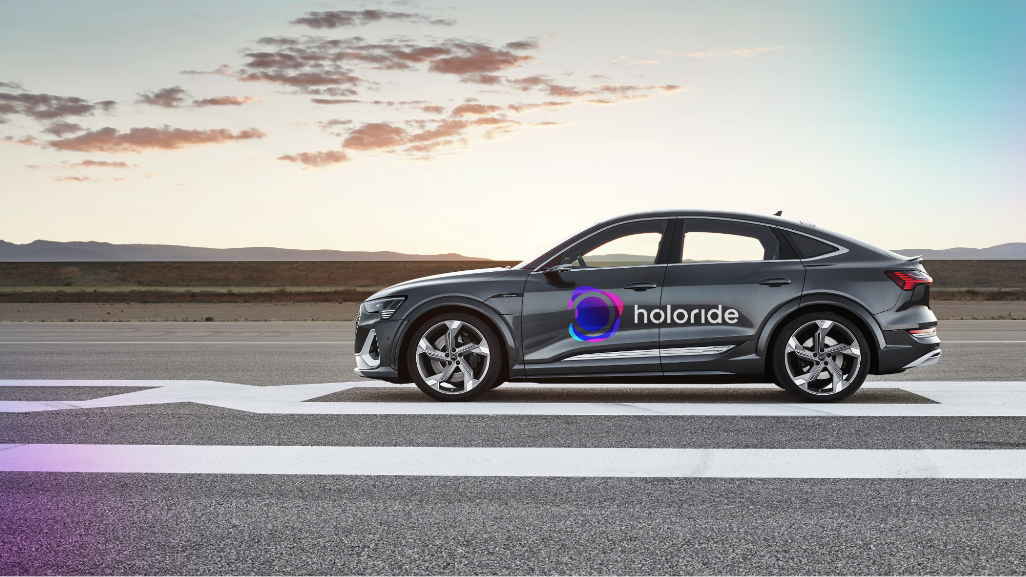 Image of a silver sedan branded with the Holoride logo driving on a road with a mountain range and sunset in the background