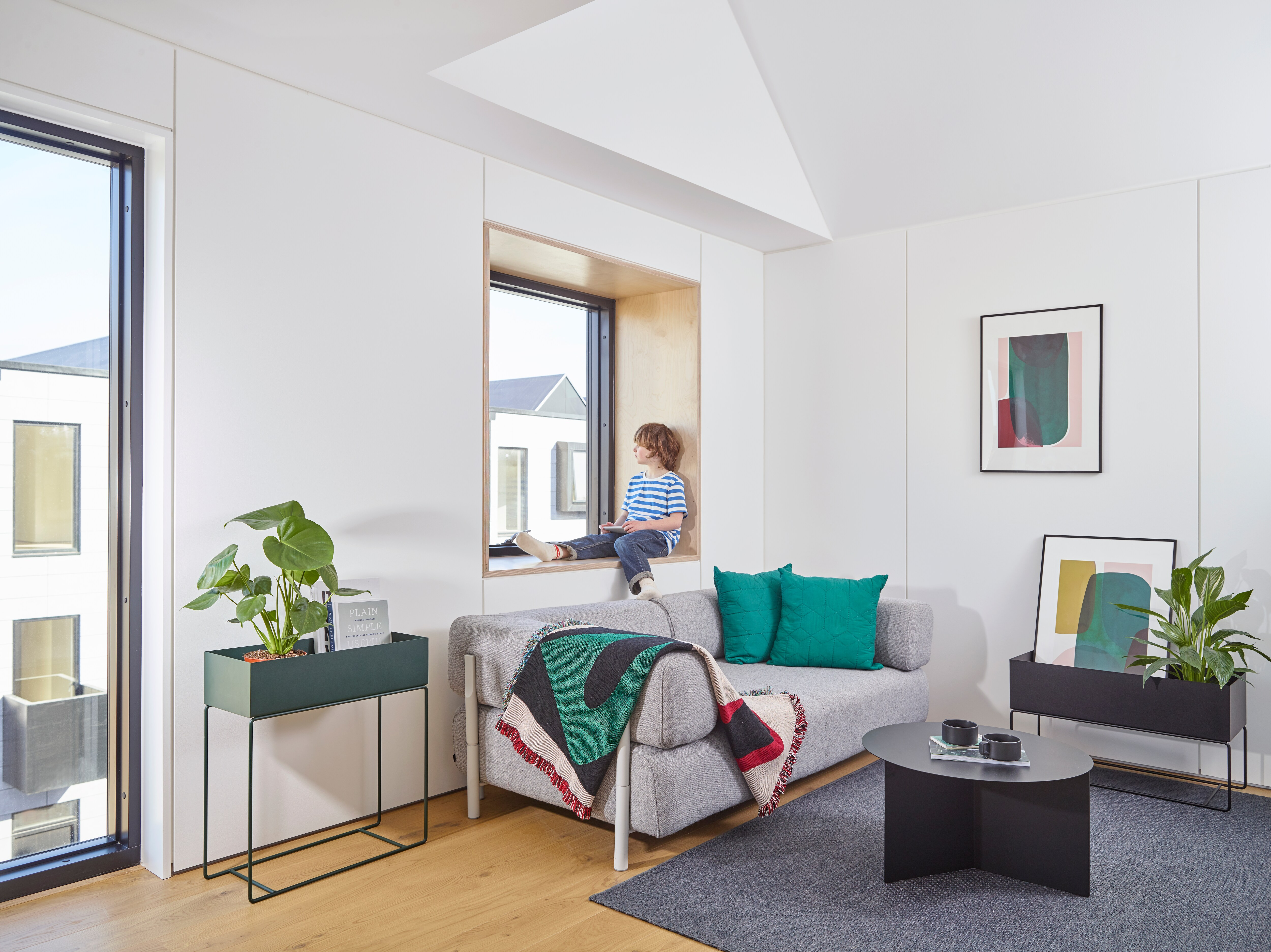 Image of a city apartment with white walls and a child sitting in the windowsill.