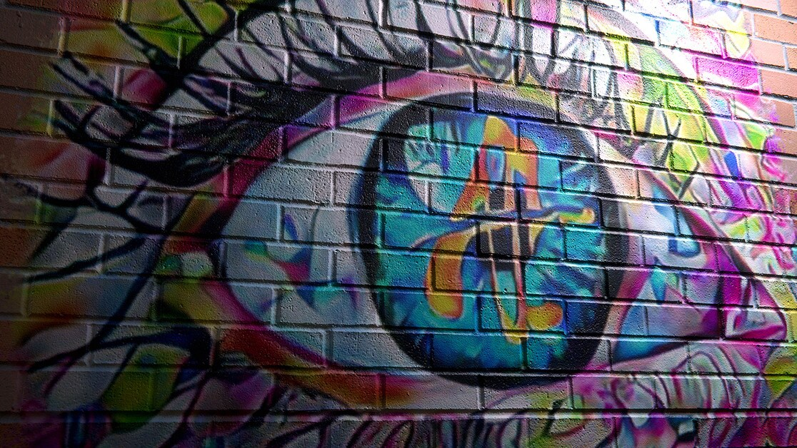 Street art depicting a large, multi-colored eye on a brick wall.