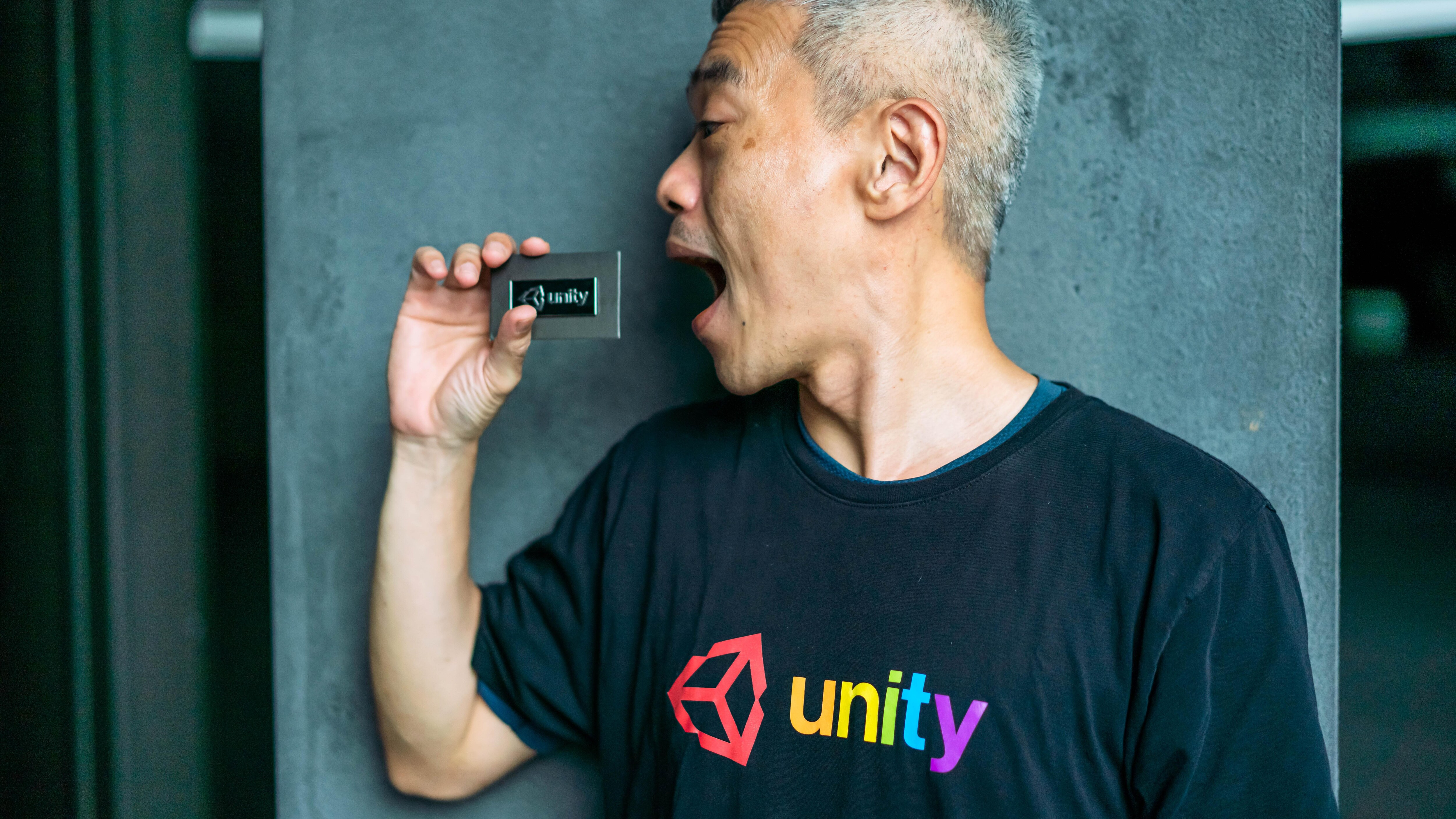 A person in a black Unity t-shirt with rainbow-colored text hold a Unity badge near his face.