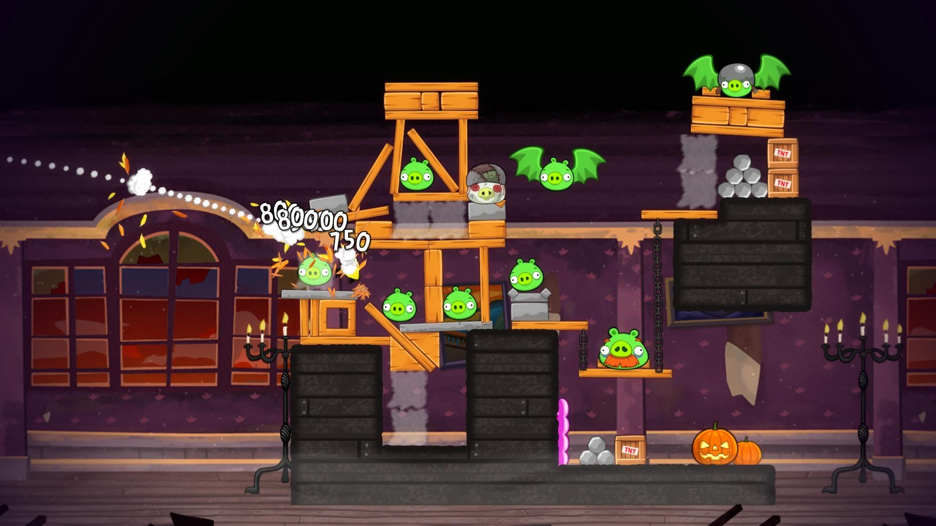 Screenshot of Angry Birds video game with a dark background and an Angry Bird crashing into a wooden tower holding up green pigs.