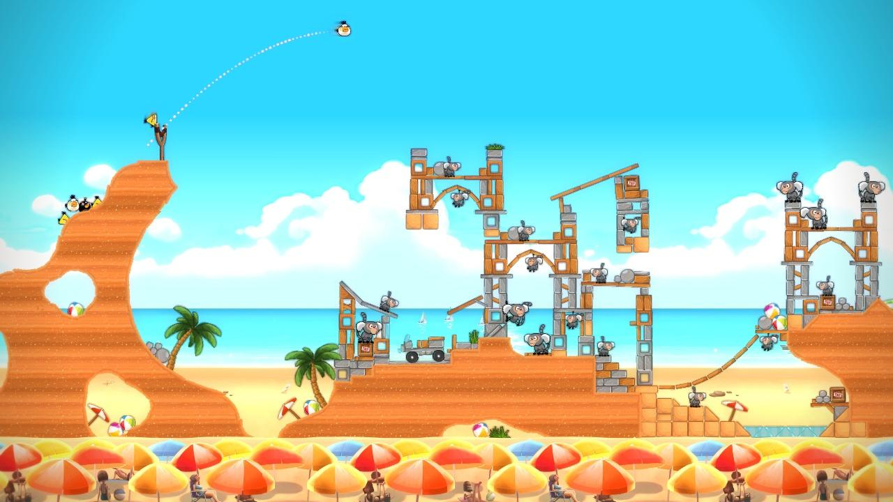 Screenshot of Angry Birds video game with a white Angry Bird being launched from a slingshot at opponents in towers on a sandy beach scene.