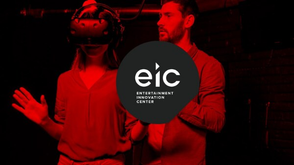 """Person with a virtual reality headset standing next to another person in a dark room with a red hue overlaid on the whole image with the logo and words, """"Entertainment Innovation Center""""."""