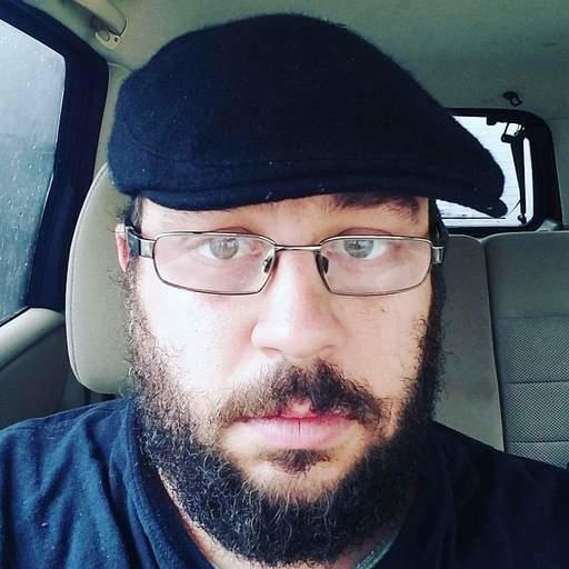 Picture of a person with a hat, glasses, and facial hair