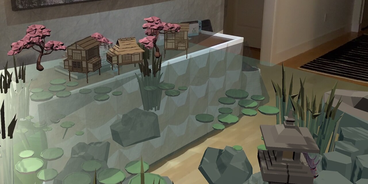 An animated pond with lily pads, rocks surrounding an in it and tall grass dotted around. One one side their are little wooden Japanese-style houses and pink cherry blossom trees. On the other there is a wooden Japanese-style tower. This animated scene has been created in AR and is being displayed on the ground and part of the wall of a room with light wooden floors and white walls.