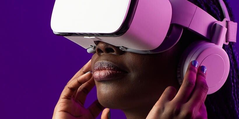 Girl wearing pink VR headset in front of a purple background.