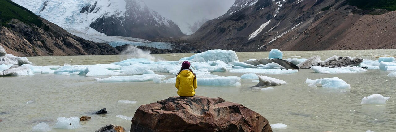 In the foreground there is a person with long brown hair and a yellow coat sitting on a large rock surrounded be smaller rocks. In the background there is chunks of ice melting into a body of water and mountains tipped with snow.