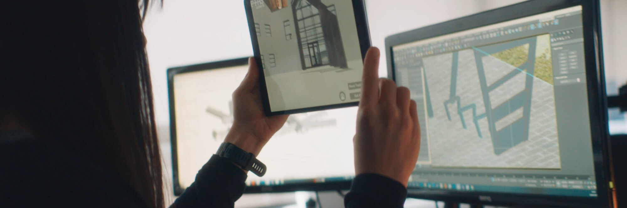 Person holding up tablet showing plans of a building. They are sitting in front of two PC screens. The on the left has an something on it that is difficult to see and the one on the right has the Unity editor open and in the editor is the building.